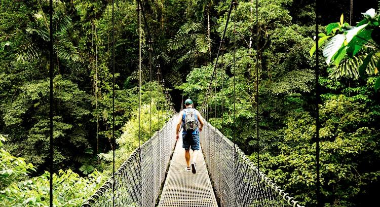 Hombre cruzando puente colgante