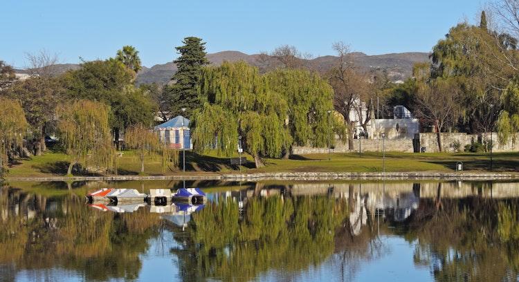 Parque con lago rodeado de arboles y montaña al fondo, Alta Gracia, Córdoba
