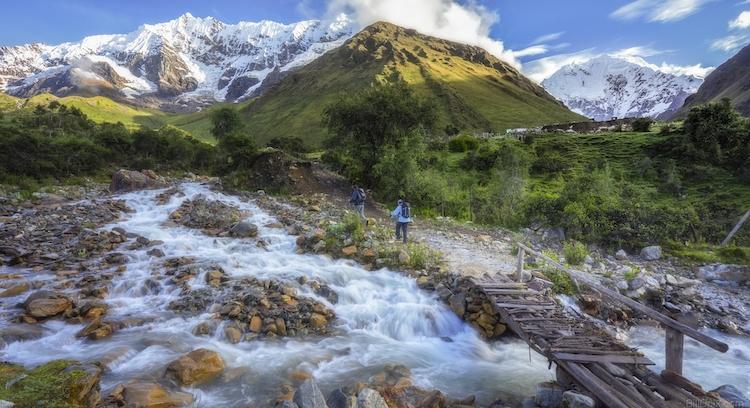 People crossing a river at the Salkantay Trek.