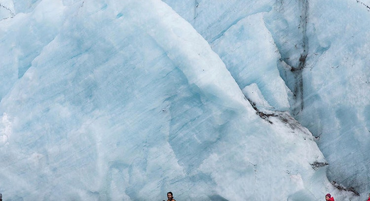 tourists sailing near grey glacier
