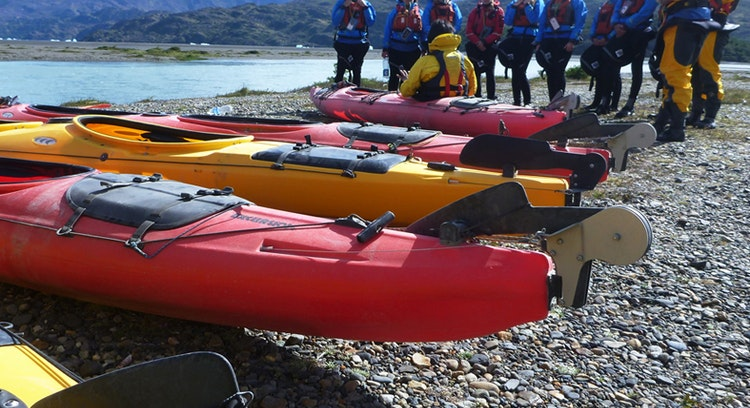 Tourists receiving instruction from the guide to kayak across the grey lake