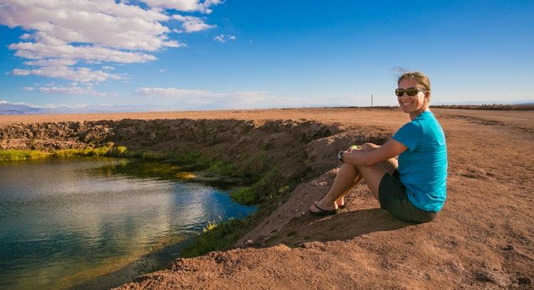 Una mujer sentada frente a la laguna cejar en San Pedro de Atacama