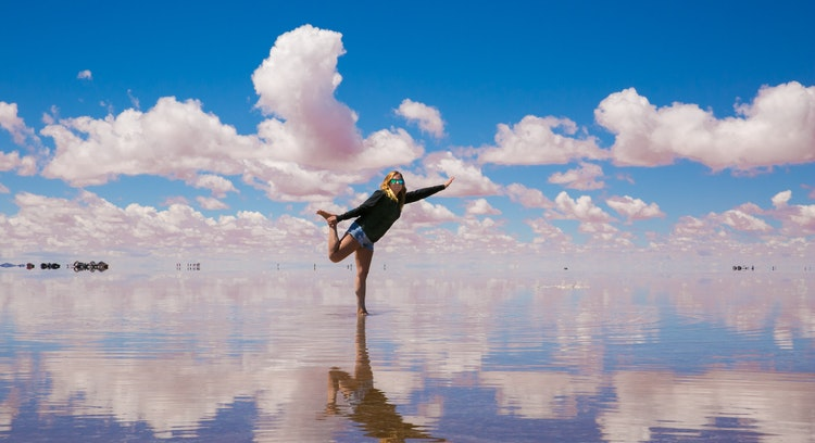 Woman posing in the Uyuni Salt Flat with mirror effect.