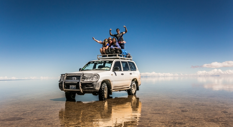 People on top of a Jeep at the Uyuni Salt Flat with mirror effect.