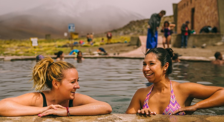 Mujeres sonriendo, tomando un baño en las termas de Polque.