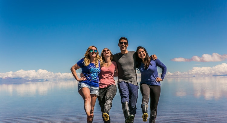 People smiling at the Uyuni Salt Flat with mirror effect.