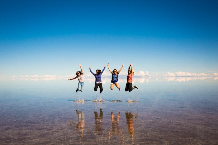 People on top of a jeep at Uyuni Salt Flat.
